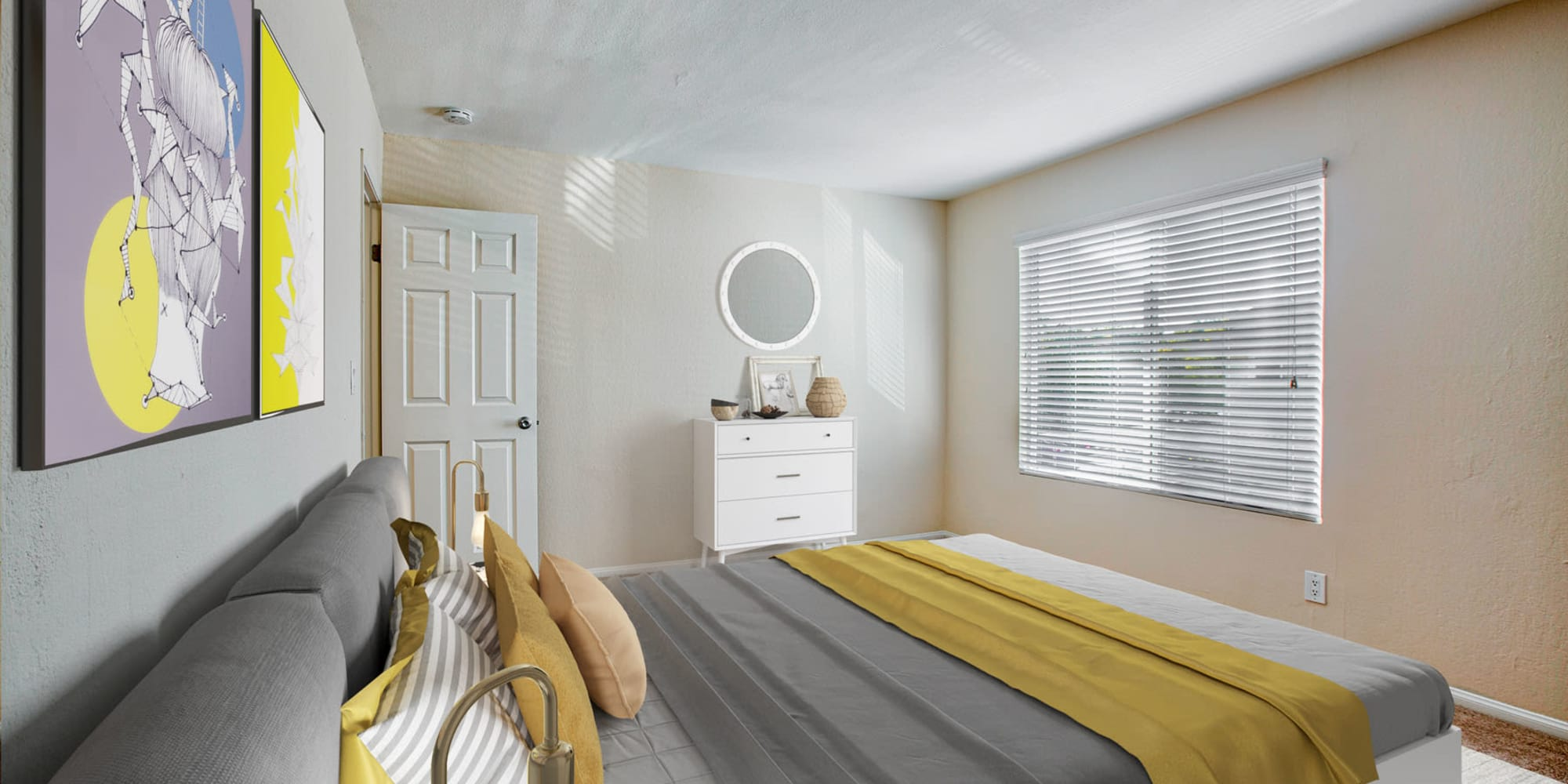 Bay window and colorful artwork in the primary bedroom of a model apartment at Pleasanton Place Apartment Homes in Pleasanton, California