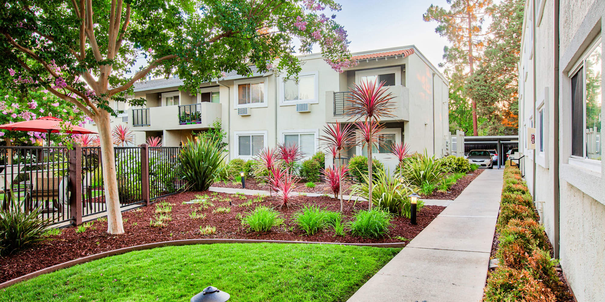 Pathways connecting various parts of the community surrounded by professionally maintained landscaping at Pleasanton Place Apartment Homes in Pleasanton, California