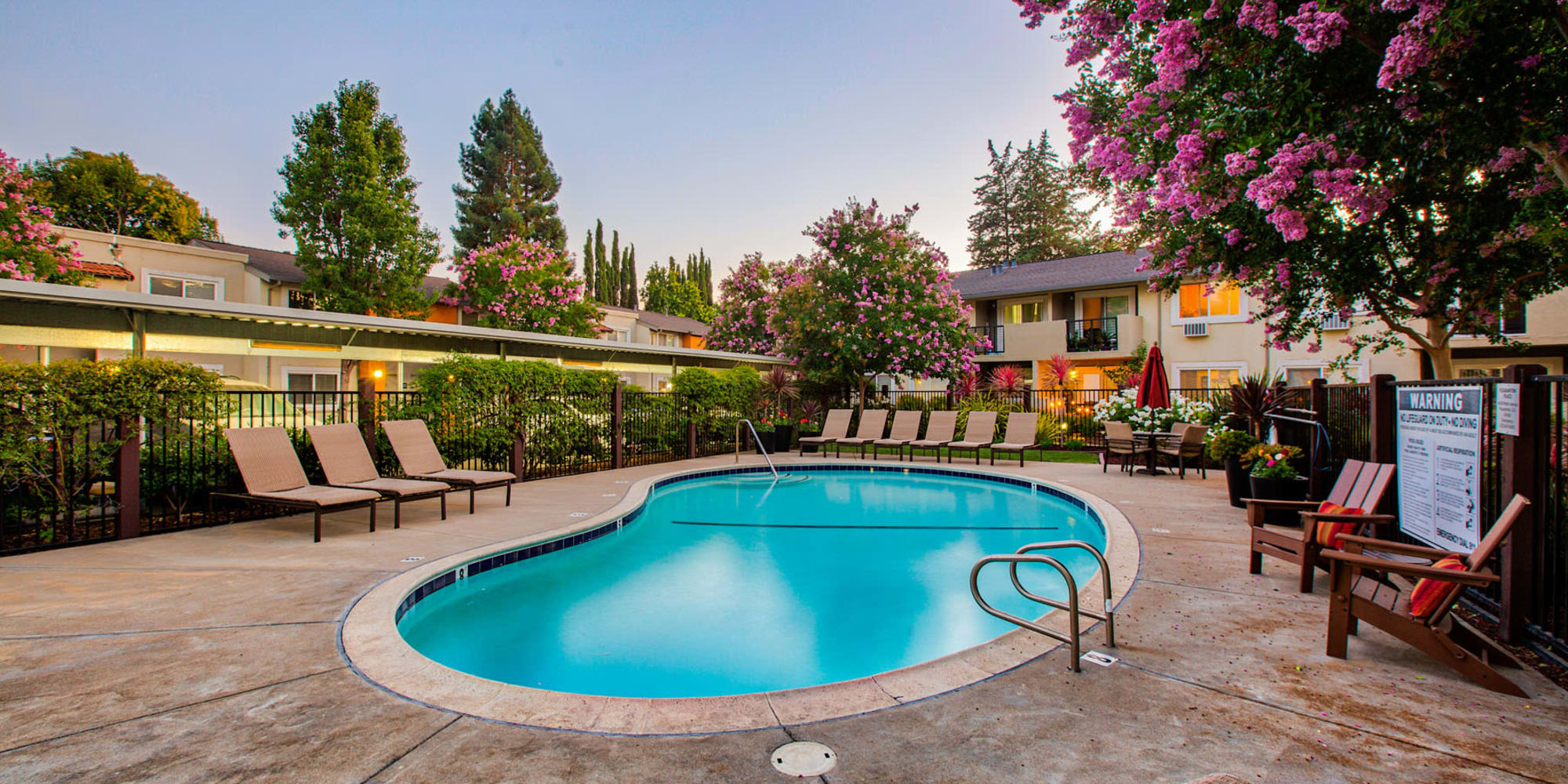 Dusk coming on with the community's evening lights at the pool area at Pleasanton Place Apartment Homes in Pleasanton, California