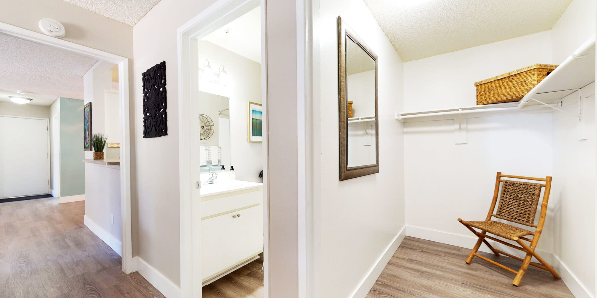 Large walk-in closet next to the bathroom in a model home with hardwood flooring throughout at Mountain Vista in Victorville, California