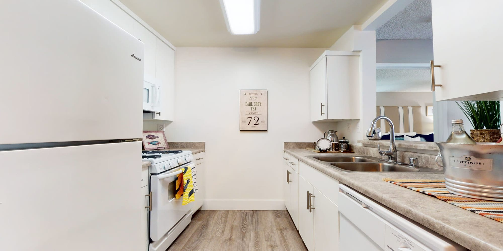 White appliances and matching cabinetry in a model apartment's kitchen at Mountain Vista in Victorville, California