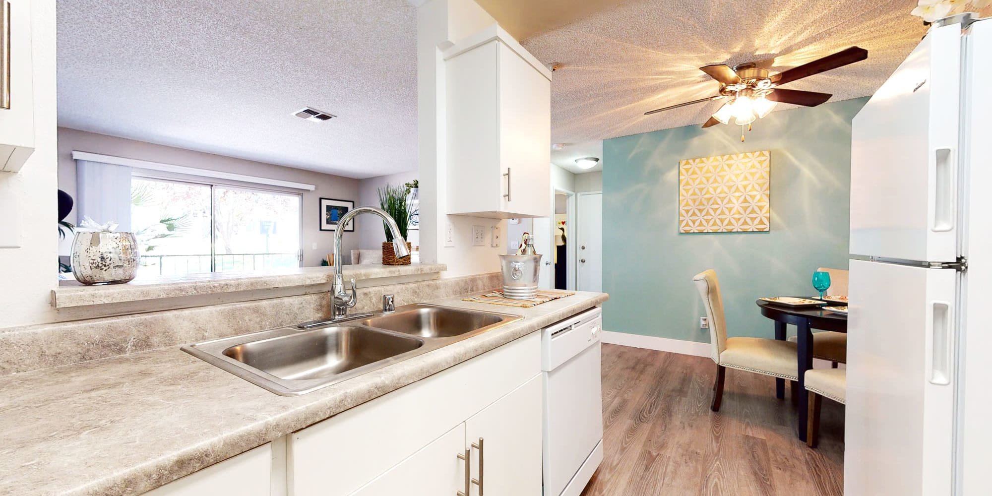 Spacious countertop with a dual-basin sink in a model apartment's kitchen at Mountain Vista in Victorville, California