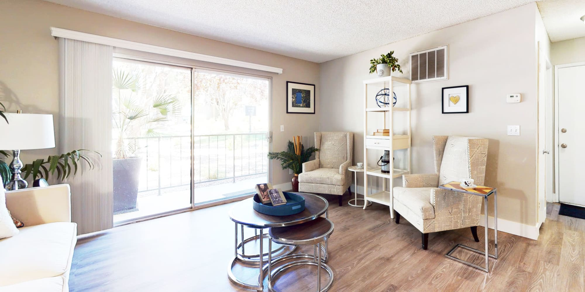 Modern furnishings in a model home's living area with a view of the private balcony outside at Mountain Vista in Victorville, California