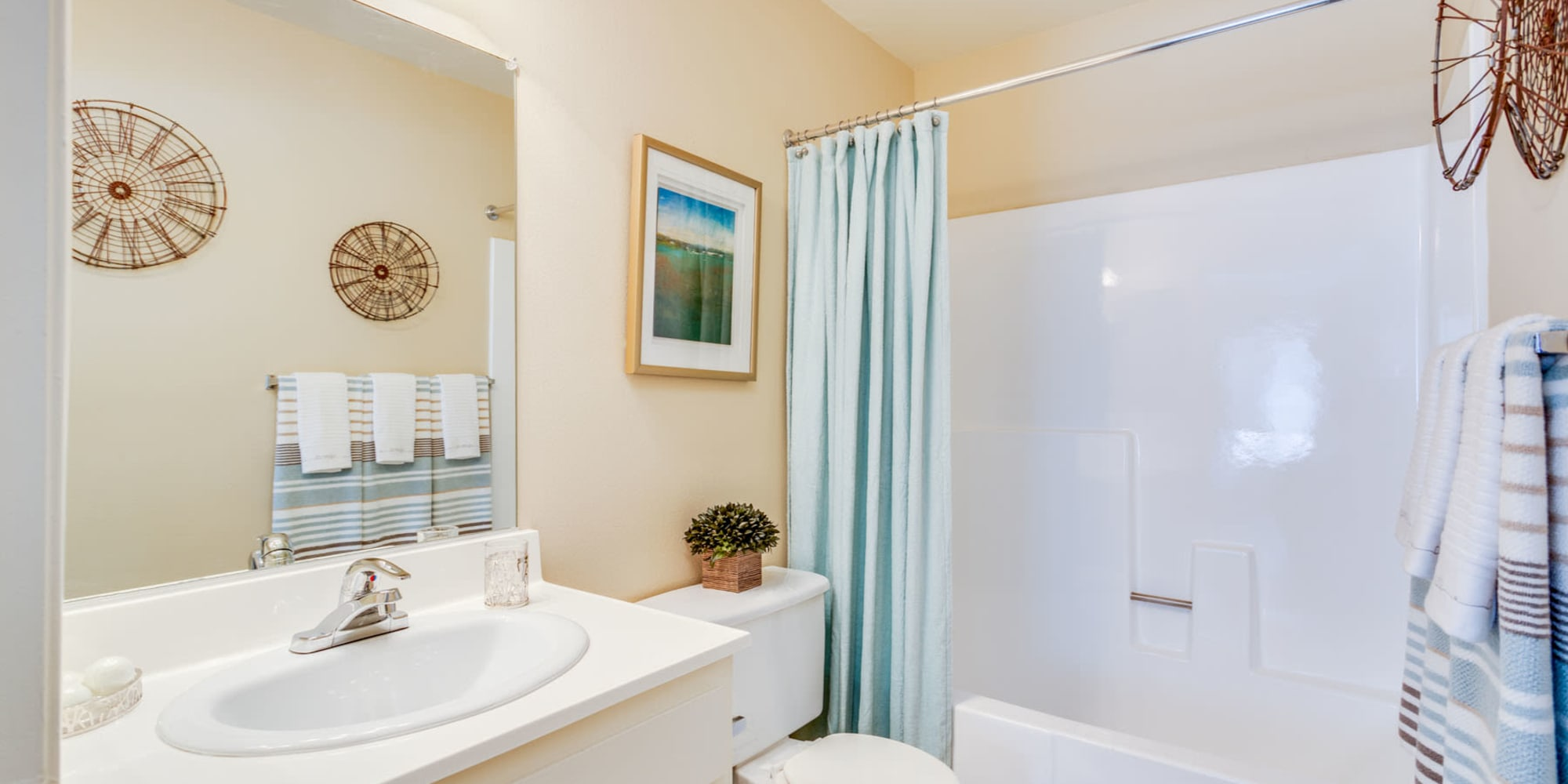 Tiled shower and a large vanity mirror in a model home at Mountain Vista in Victorville, California