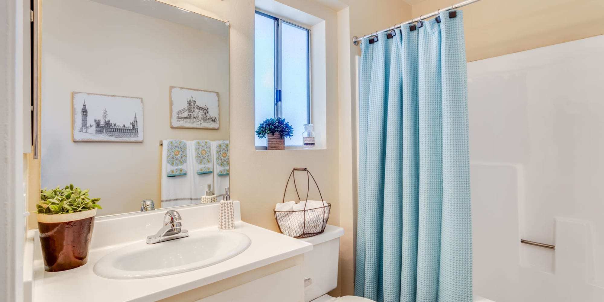 Well-lit bathroom with a privacy window in a model apartment at Mountain Vista in Victorville, California
