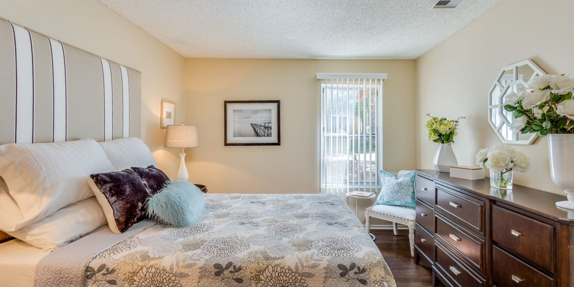 Well-furnished primary bedroom with a bay window and vertical blinds at Mountain Vista in Victorville, California