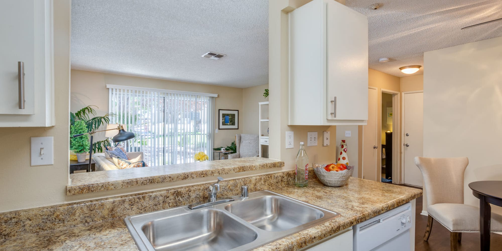 Open-concept kitchen with a view of the living area in a model home at Mountain Vista in Victorville, California