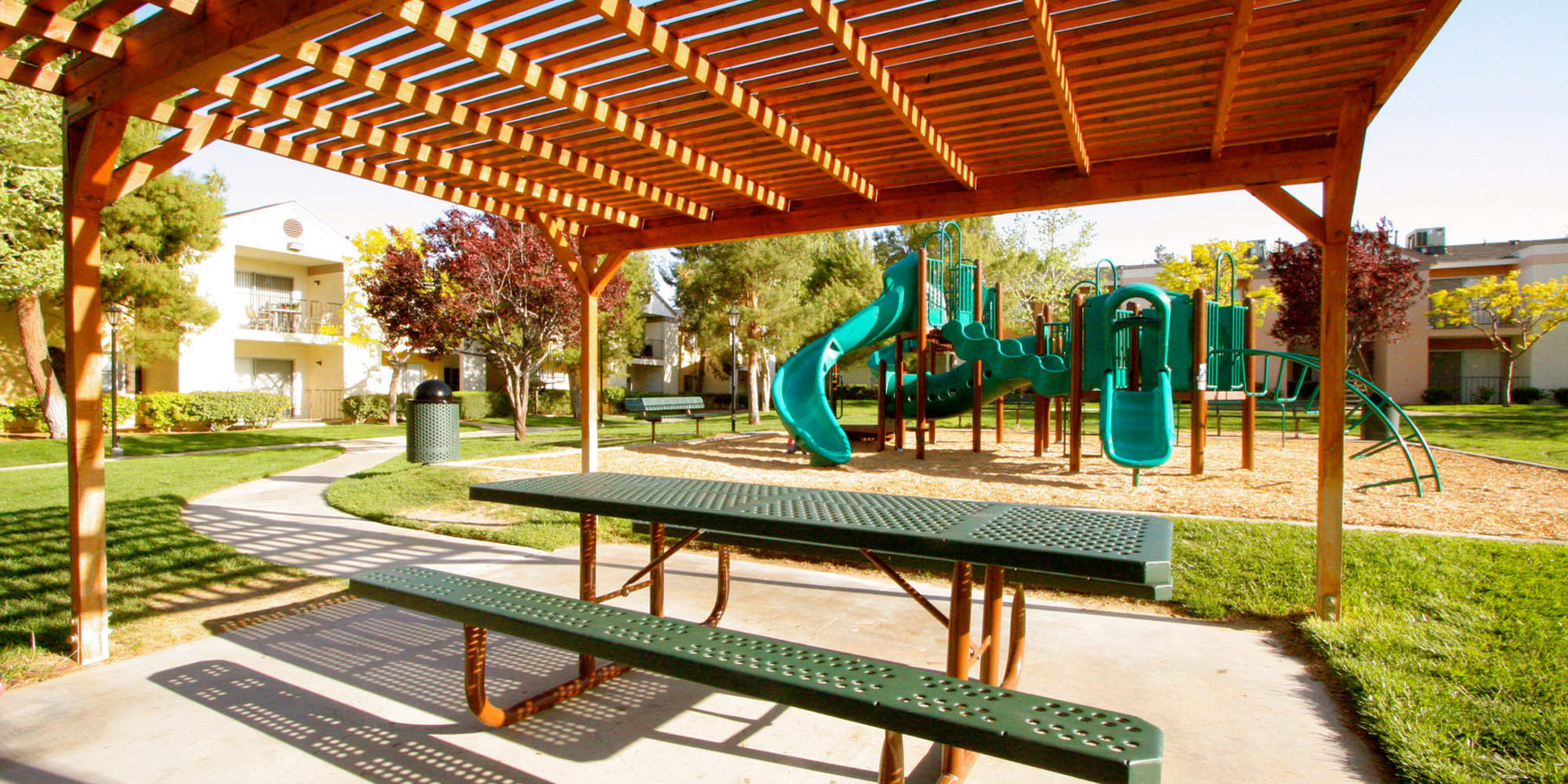 Picnic bench and table under a pergola near the playground at Mountain Vista in Victorville, California