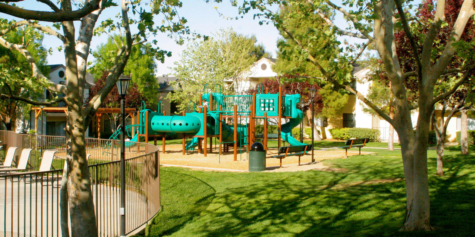 Children's playground surrounded by green grass and leafy trees at Mountain Vista in Victorville, California