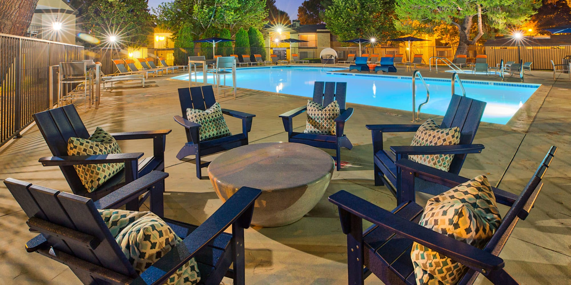Adirondack lounge chairs around a drink table near the swimming pool at dusk at Mountain Vista in Victorville, California