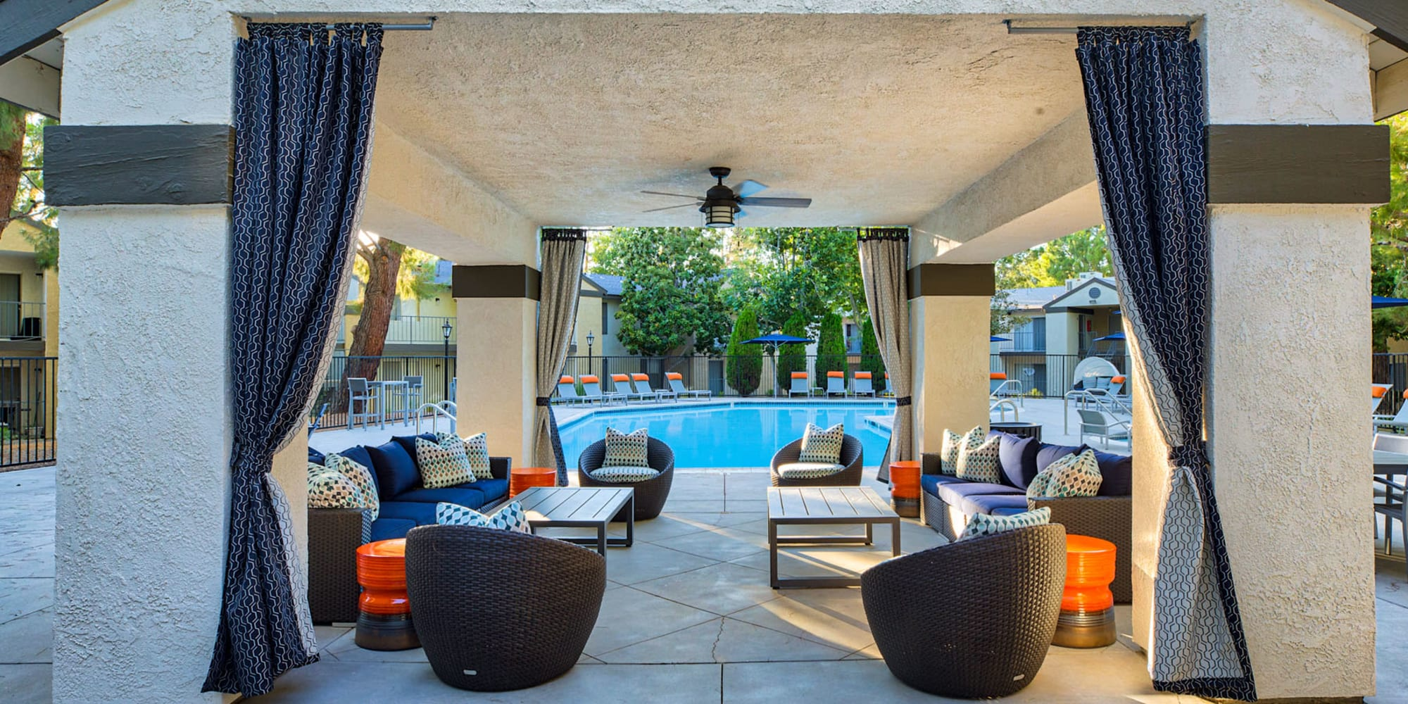 Covered poolside lounge with a ceiling fan overhead at Mountain Vista in Victorville, California