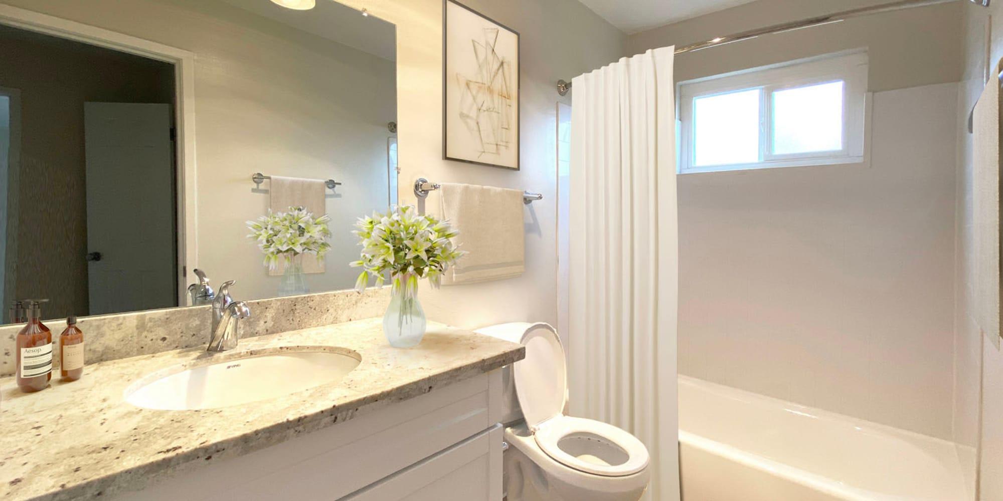 Granite countertop and a large vanity mirror in a model apartment's bathroom at Pleasanton Heights in Pleasanton, California