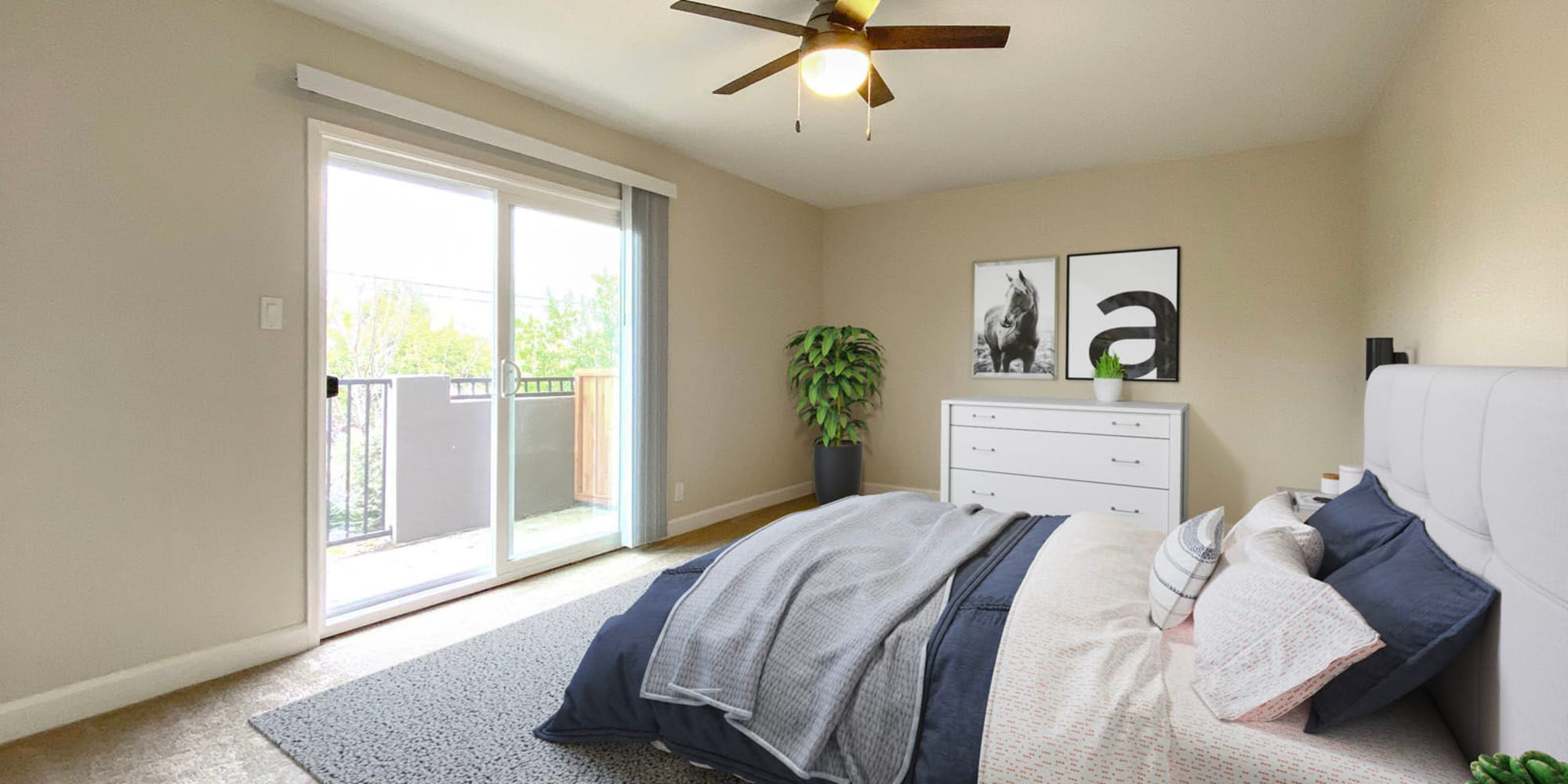 Model apartment's bedroom with a ceiling fan and private balcony outside at Pleasanton Heights in Pleasanton, California