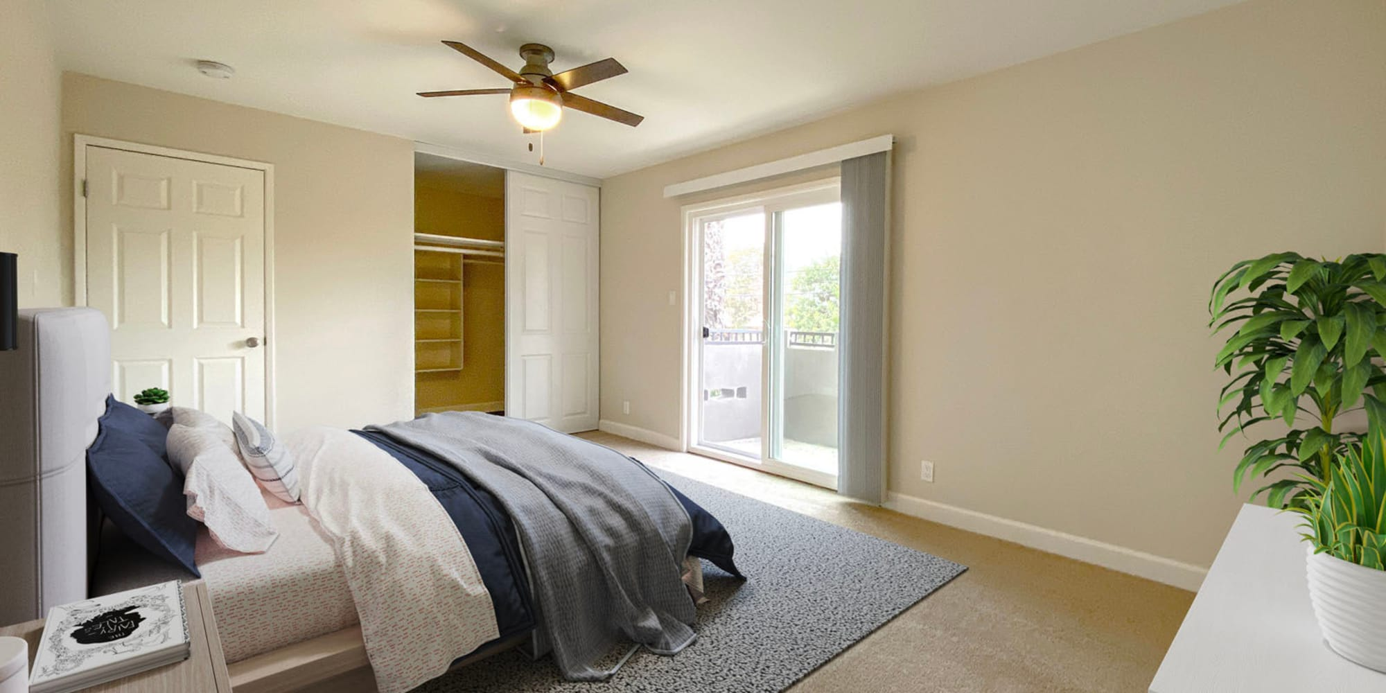 Ample closet space and plush carpeting in the well-furnished primary suite of a model apartment at Pleasanton Heights in Pleasanton, California