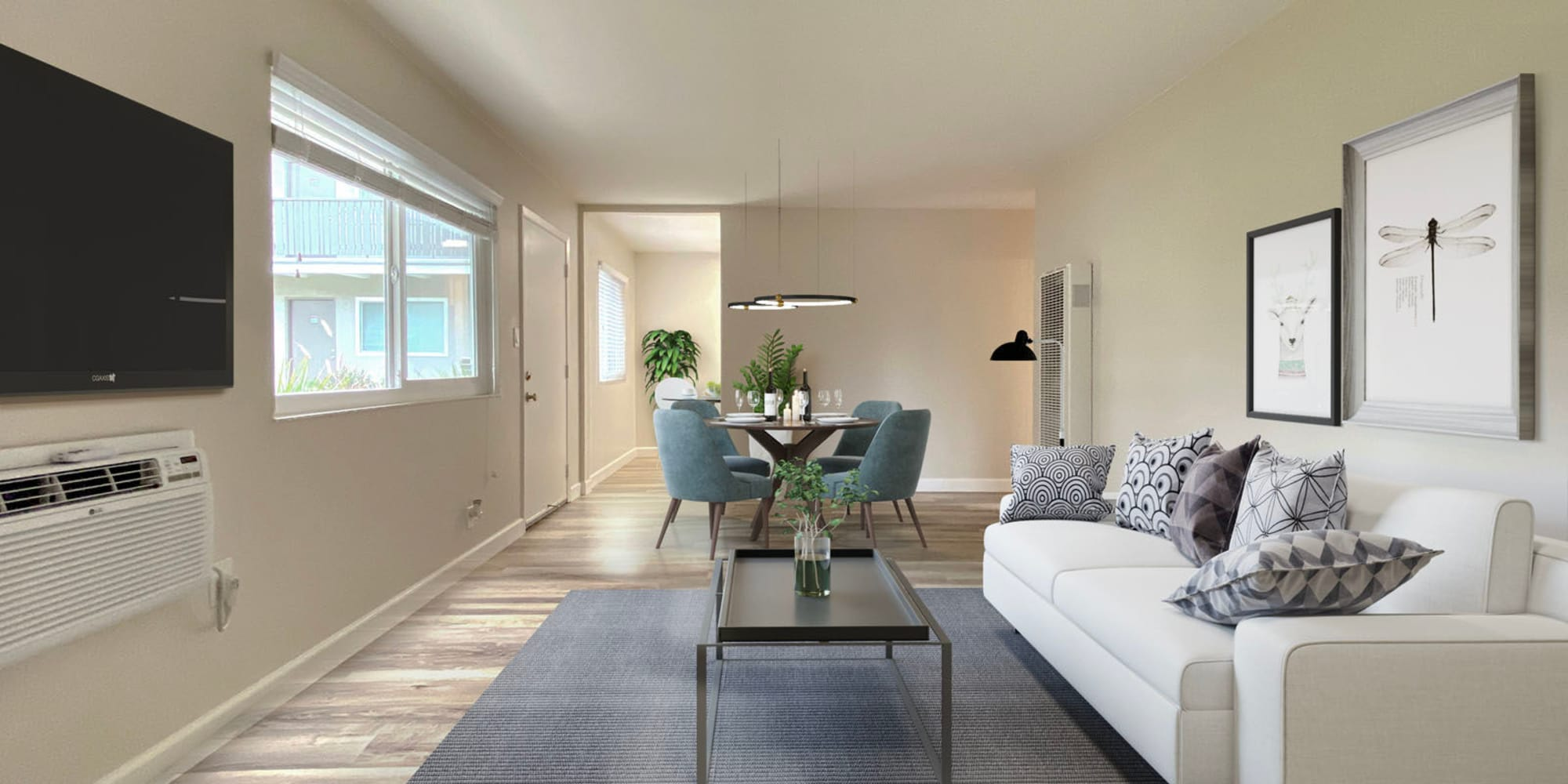Model apartment's spacious open-concept living space with modern furnishings and a wall-mounted flatscreen TV at Pleasanton Heights in Pleasanton, California