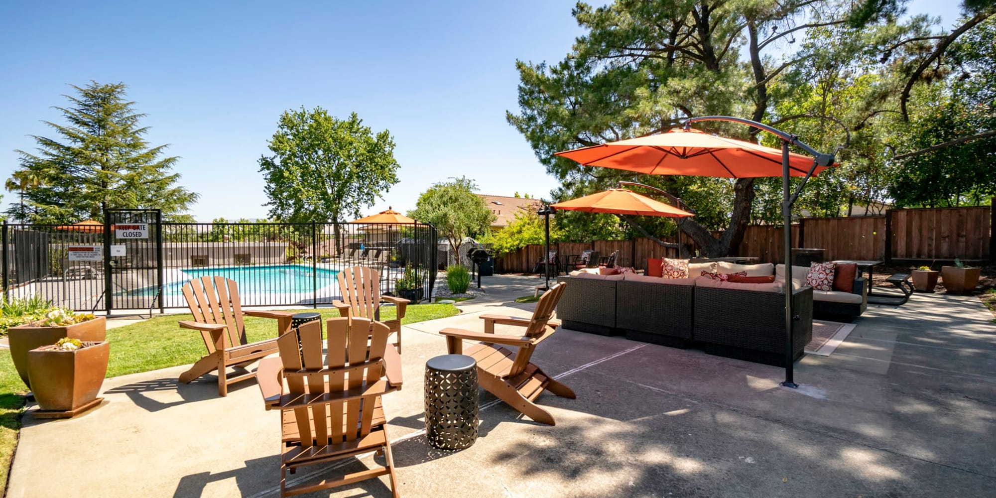 Adirondack chairs with a view of the swimming pool near the barbecue area at Pleasanton Heights in Pleasanton, California