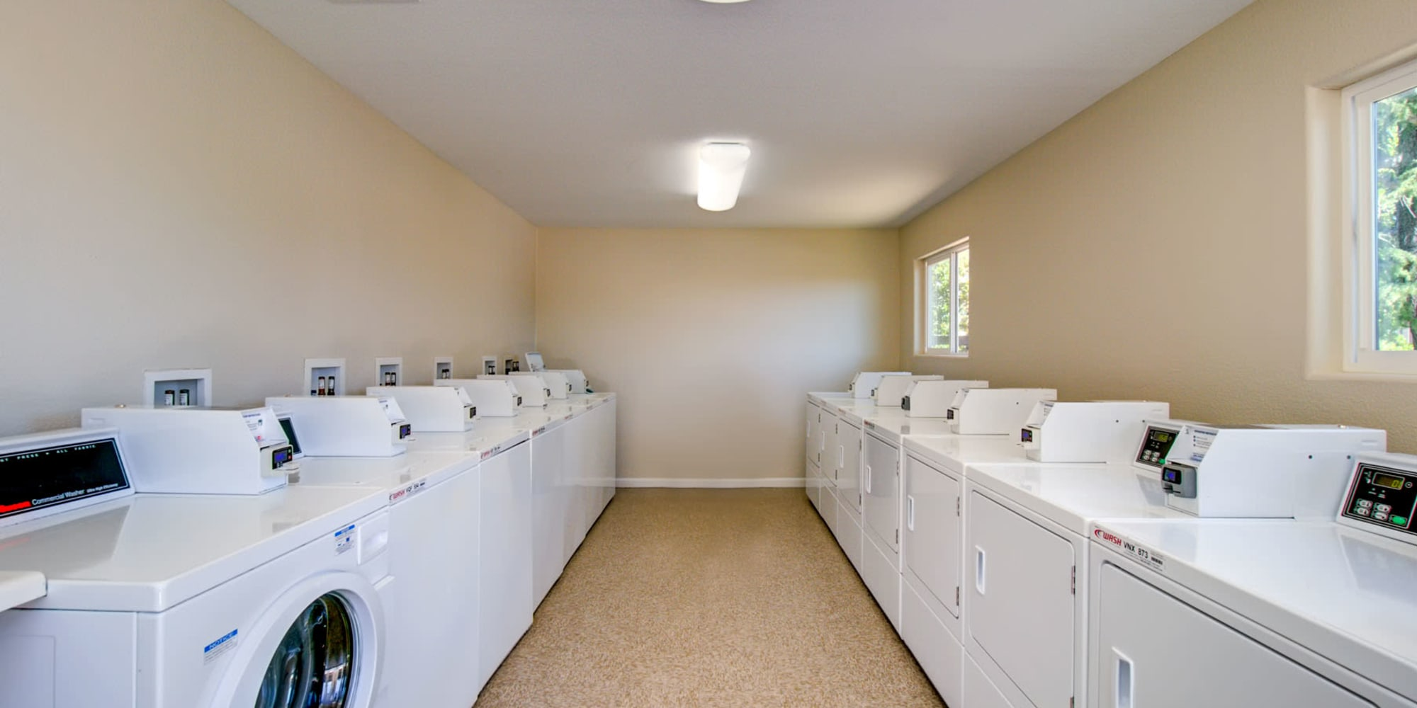 Rows of laundry machines in the onsite clothes care center at Pleasanton Heights in Pleasanton, California