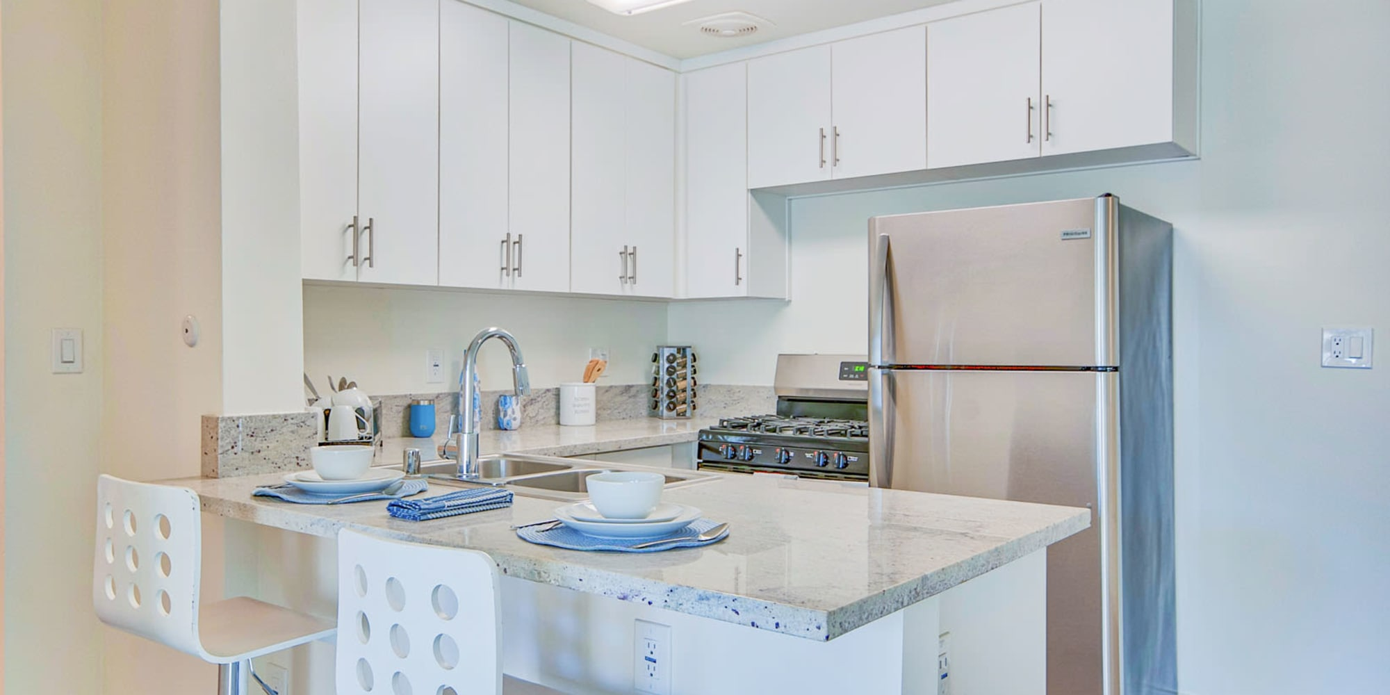 Model apartment's kitchen with stainless-steel appliances and a breakfast bar at Villa Vicente in Los Angeles, California