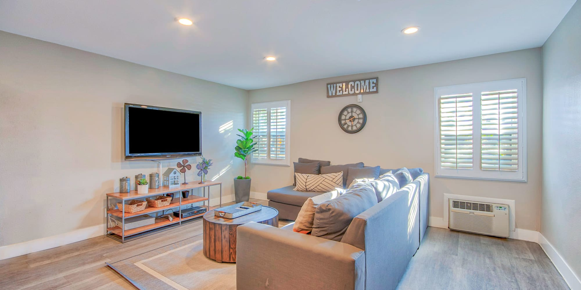 Wall-mounted flatscreen TV and comfortable lounge area in the clubhouse at Villa Vicente in Los Angeles, California