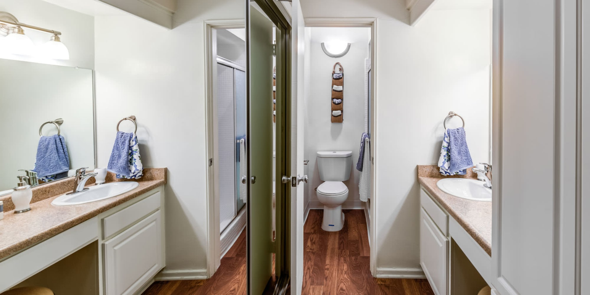 Mirrored closet doors and a large vanity mirror in the primary bathroom of a model apartment at Villa Vicente in Los Angeles, California