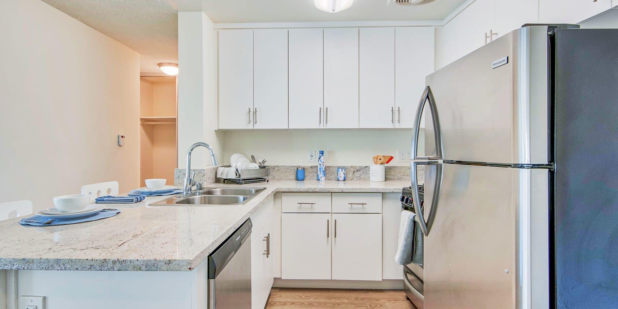 Bright white cabinetry and granite countertops in a model home's kitchen at Villa Vicente in Los Angeles, California