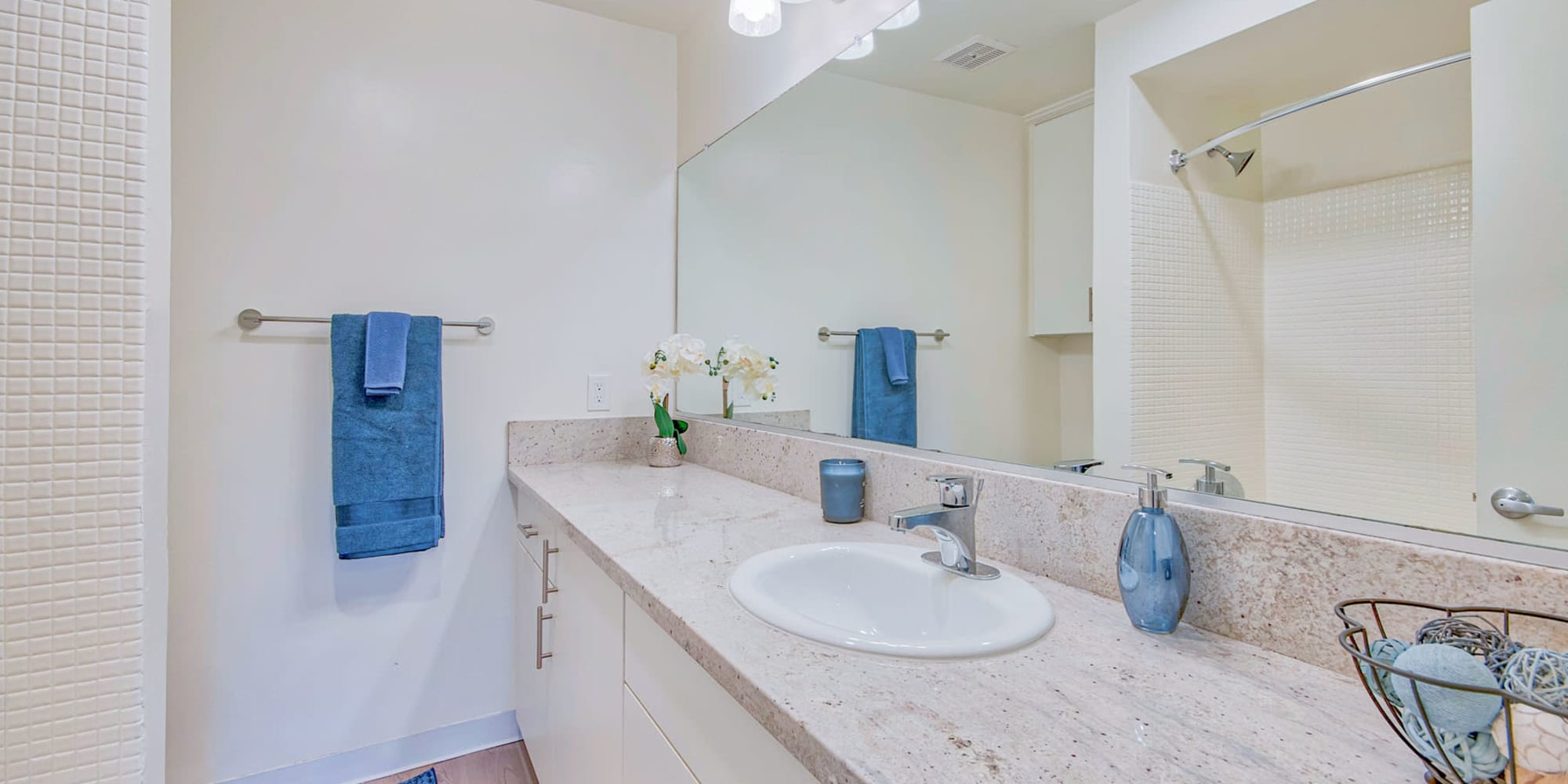 Expansive granite countertop and a custom tiled shower in a model home's bathroom at Villa Vicente in Los Angeles, California