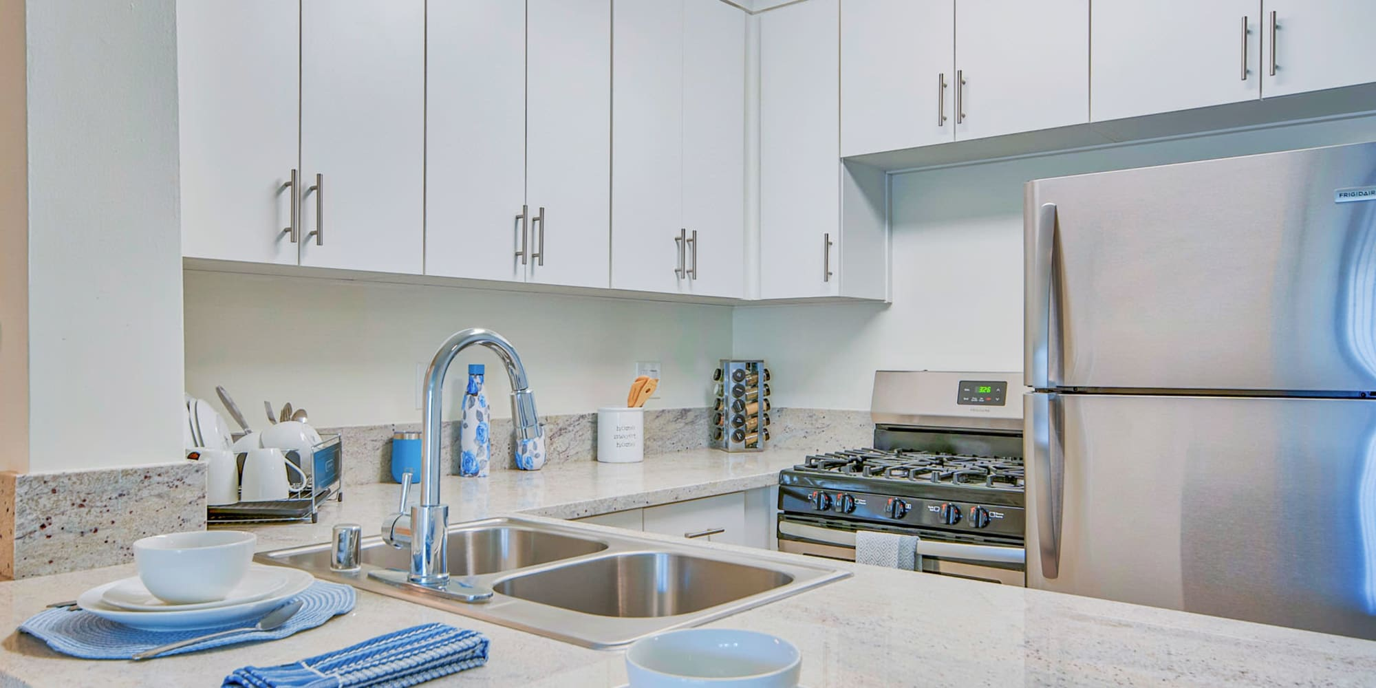 Granite countertops and a dual-basin sink in a model home's kitchen at Villa Vicente in Los Angeles, California