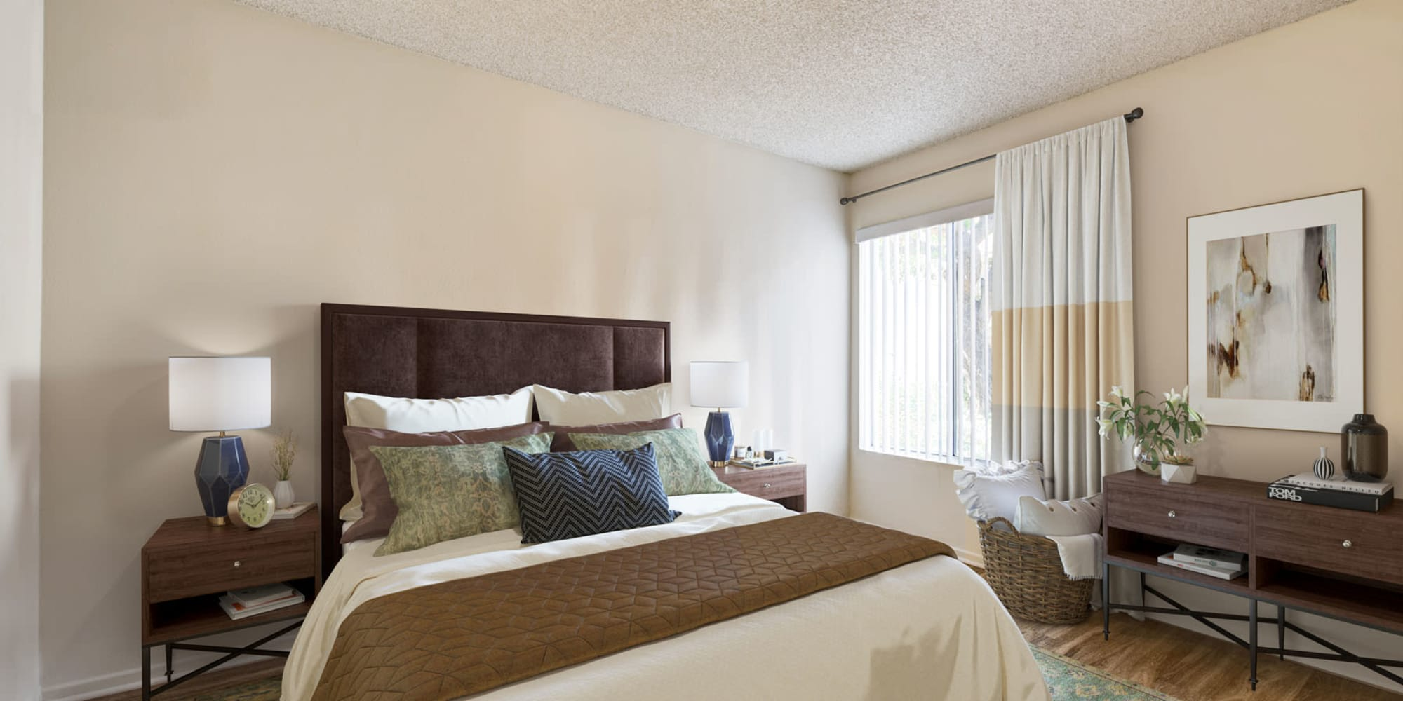 Well-furnished bedroom with a large bay window and vertical blinds in a model home at Village Pointe in Northridge, California
