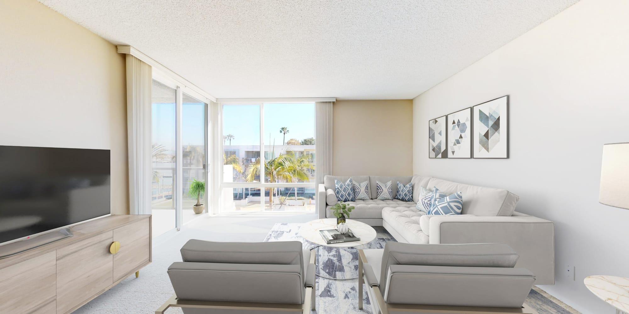 Living room with floor-to-ceiling windows and balcony with views of the marina at Waters Edge at Marina Harbor in Marina del Rey, California