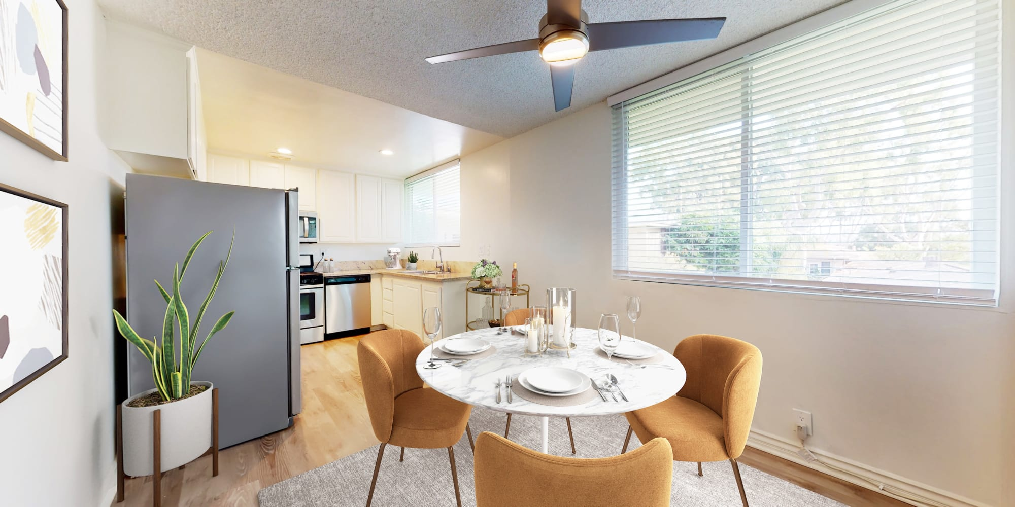 Dining room and kitchen in a two-bedroom apartment home at Sunset Barrington Gardens in Los Angeles, California