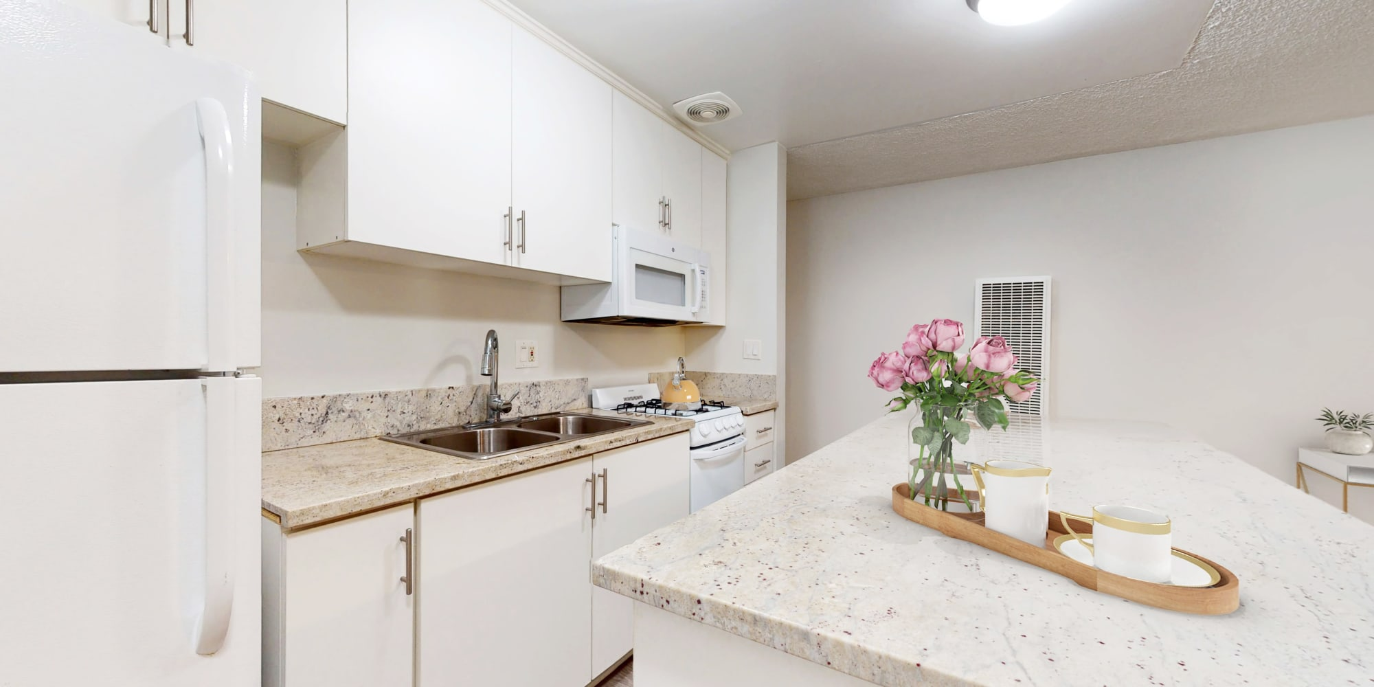 Kitchenette with white beautiful cabinets and island of a Studio model apartment at Casa Granada in Los Angeles, California
