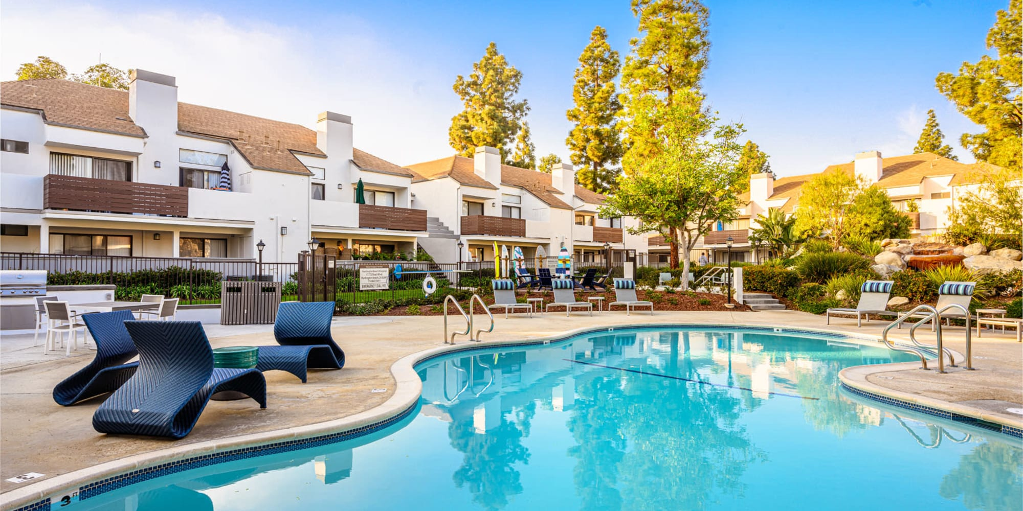 Inviting swimming pool with resident buildings and mature trees in the background at Sendero Huntington Beach in Huntington Beach, California