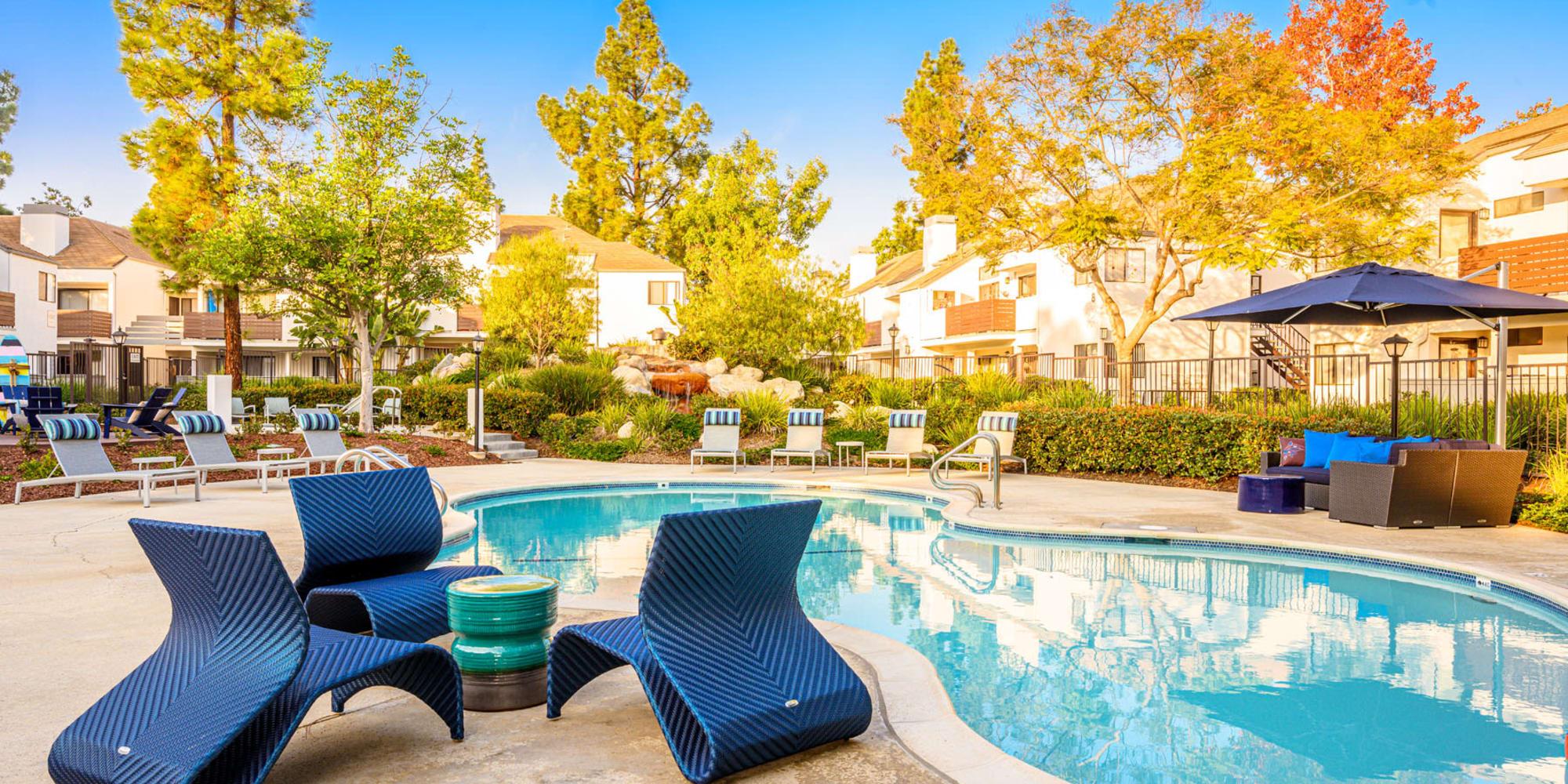 Avant garde chairs and a small table near the swimming pool at Sendero Huntington Beach in Huntington Beach, California