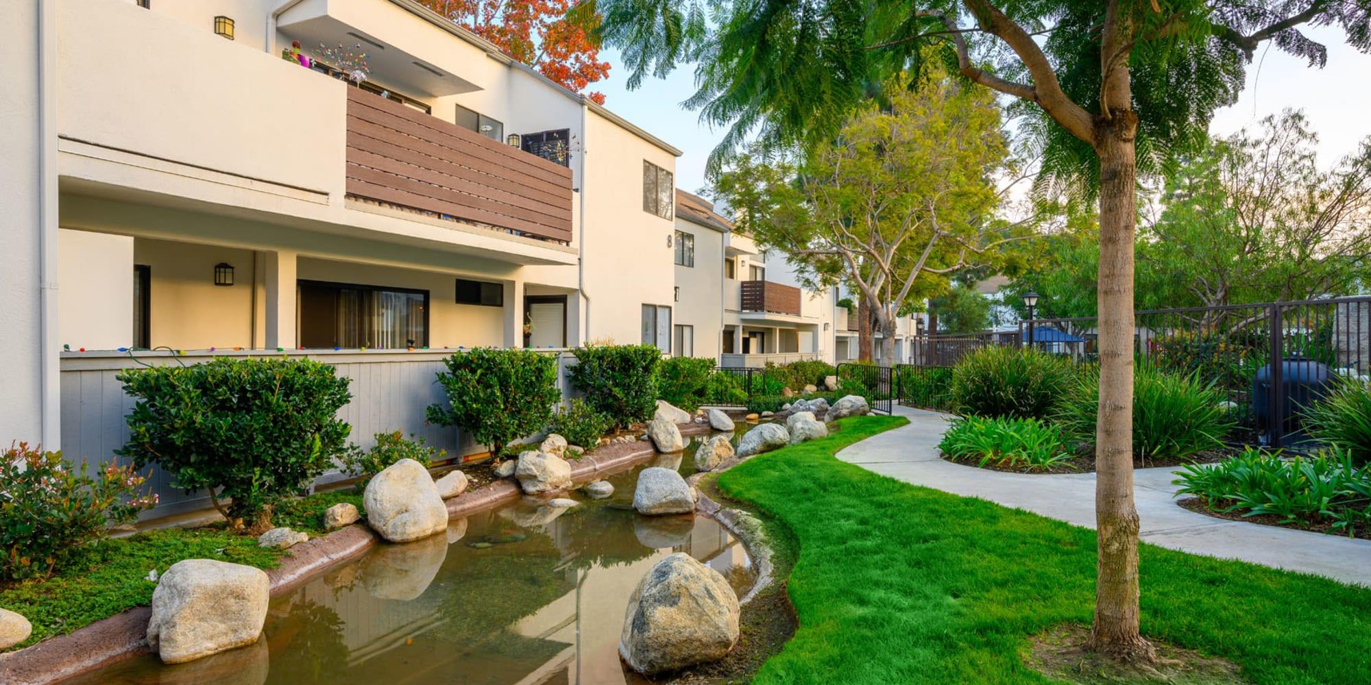Lush green grass and a small pond outside resident buildings at Sendero Huntington Beach in Huntington Beach, California