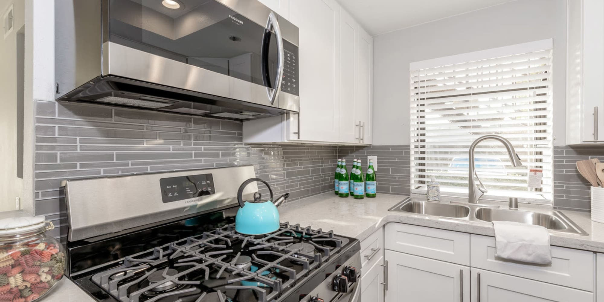 Model home's kitchen with sleek looking white cabinets and stainless steel appliances at Sendero Huntington Beach in Huntington Beach, California