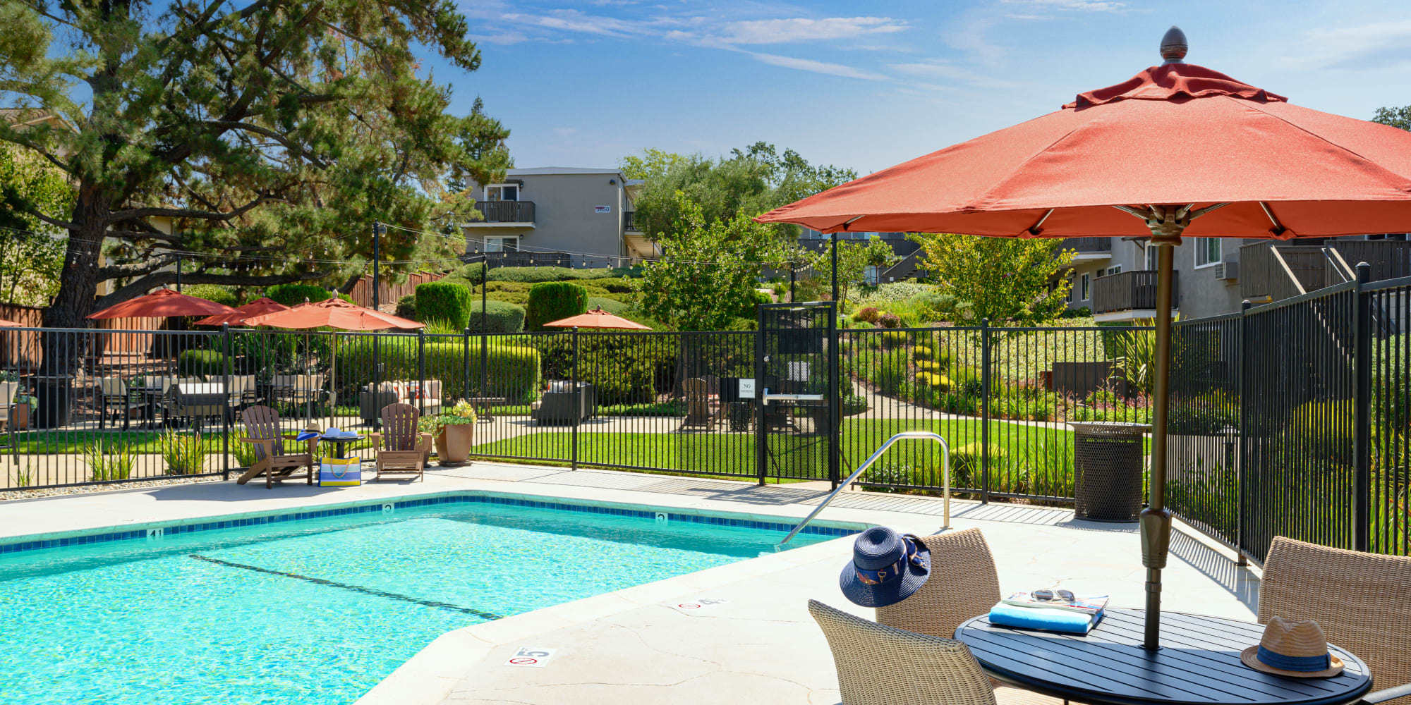 Resort-style swimming pool with shaded seating nearby at Pleasanton Heights in Pleasanton, California