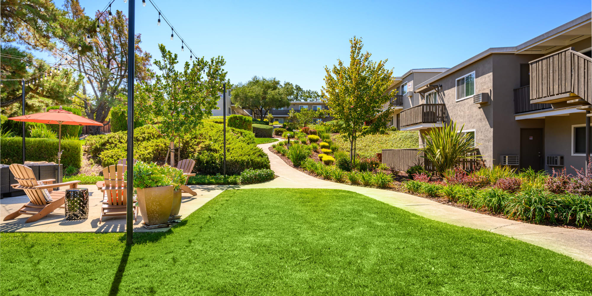 Scenic view of the community with grassy lawn and lounge area with umbrella at Pleasanton Heights in Pleasanton, California