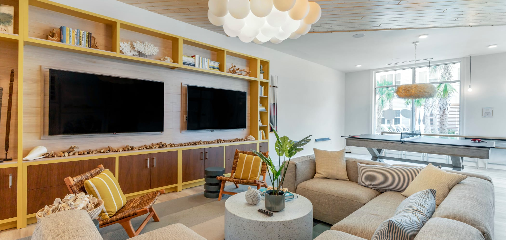 Community living room with TVs at UNCOMMON Wilmington in Wilmington, North Carolina
