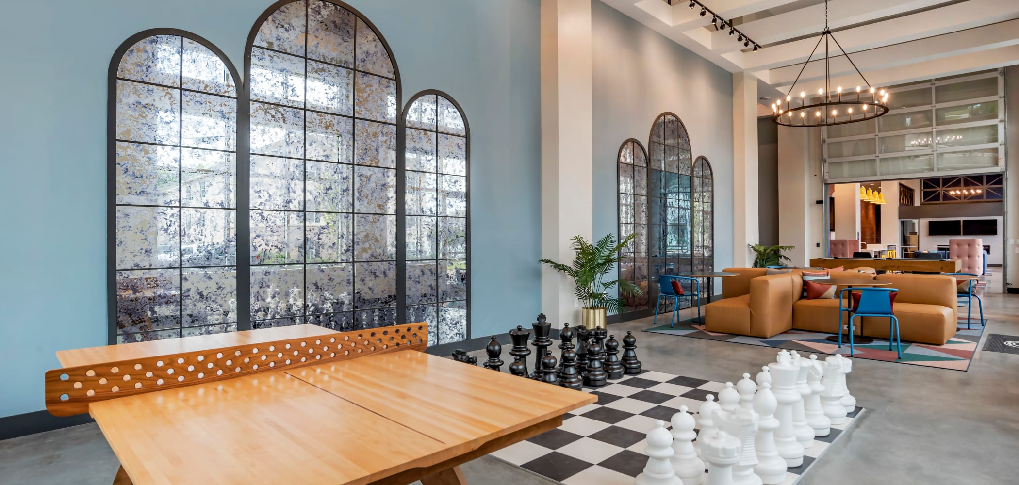 Clubhouse area with chairs, tables, and giant chess at UNCOMMON Auburn in Auburn, Alabama