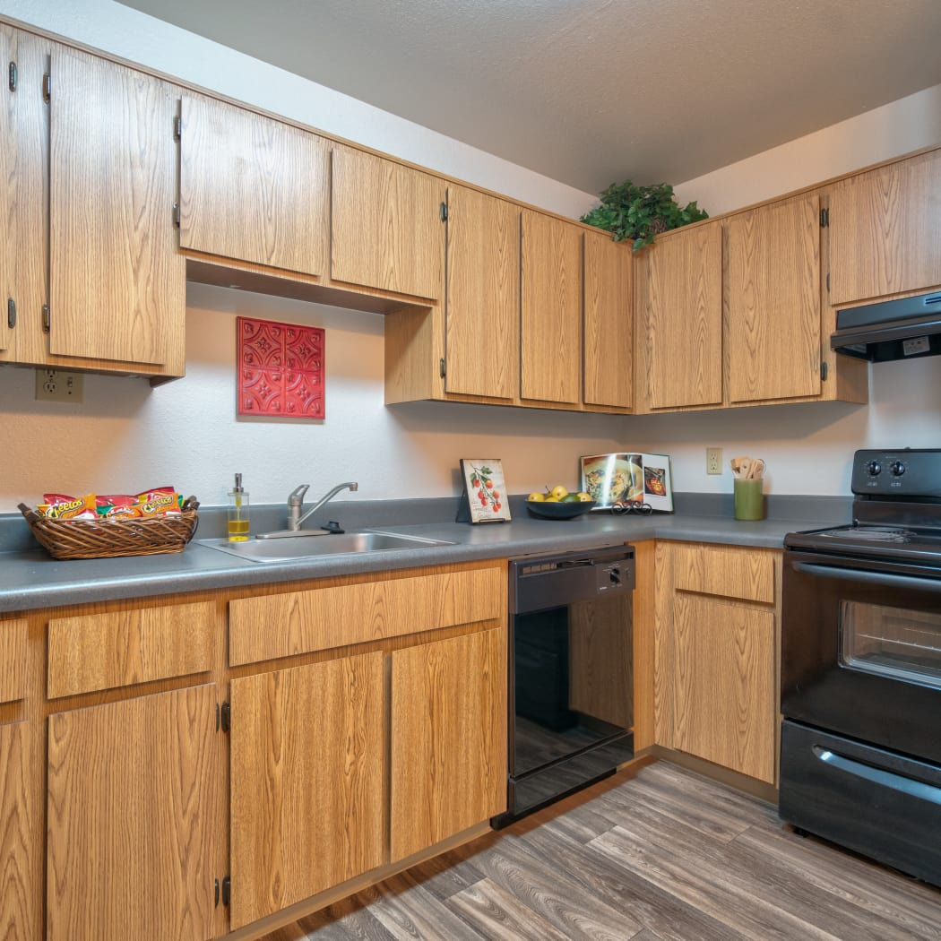 Kitchen with custom countertops overlooking a spacious living room at Argenta Apartment Homes in Mesa, Arizona