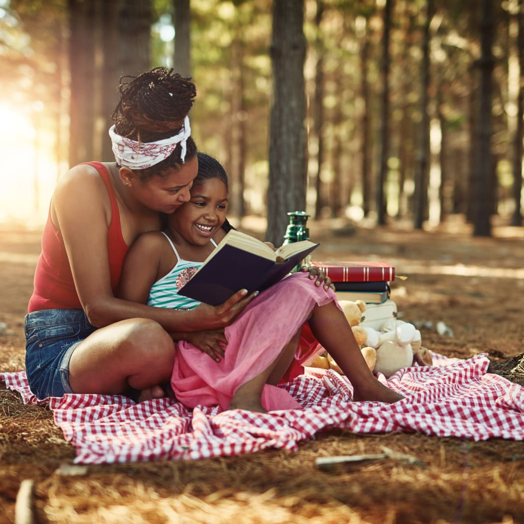 Mother and daughter reading together at a park in Indian Head, Maryland near Charles Landing South