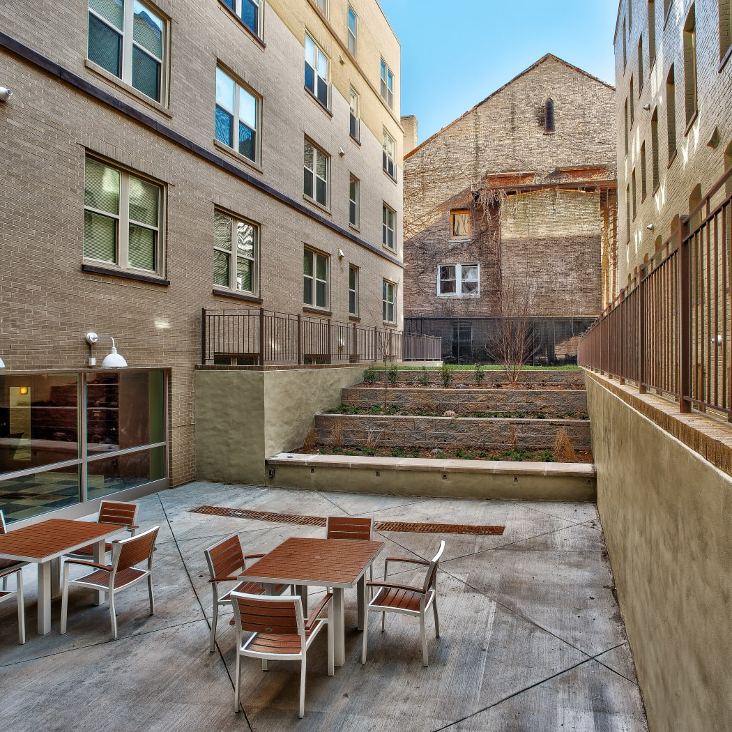 Outdoor patio seating at Monsenor Romero Apartments in Washington, District of Columbia