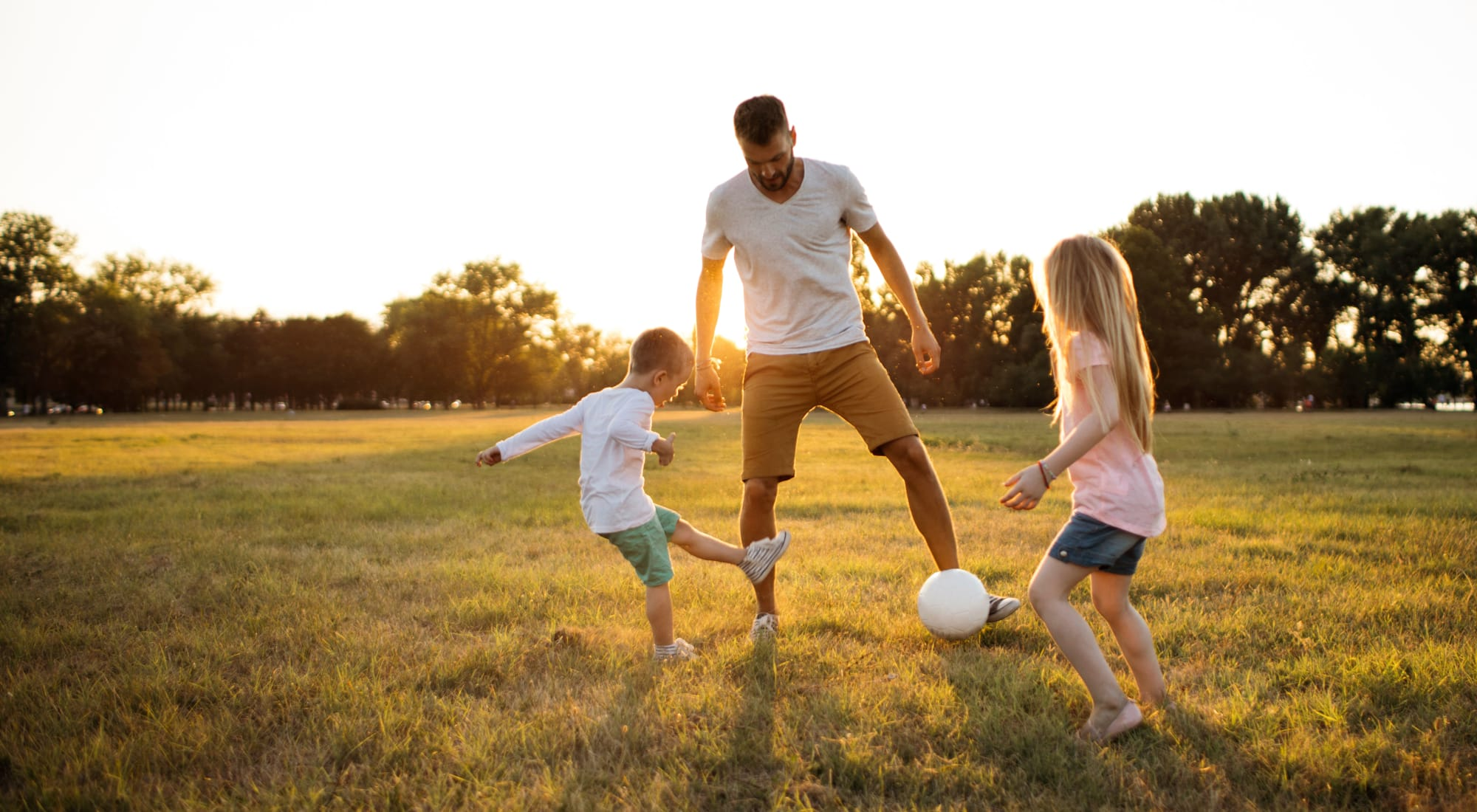 Father playing soccer with his children outside near The Ranch at Bear Creek Apartments & Townhomes in Lakewood, Colorado