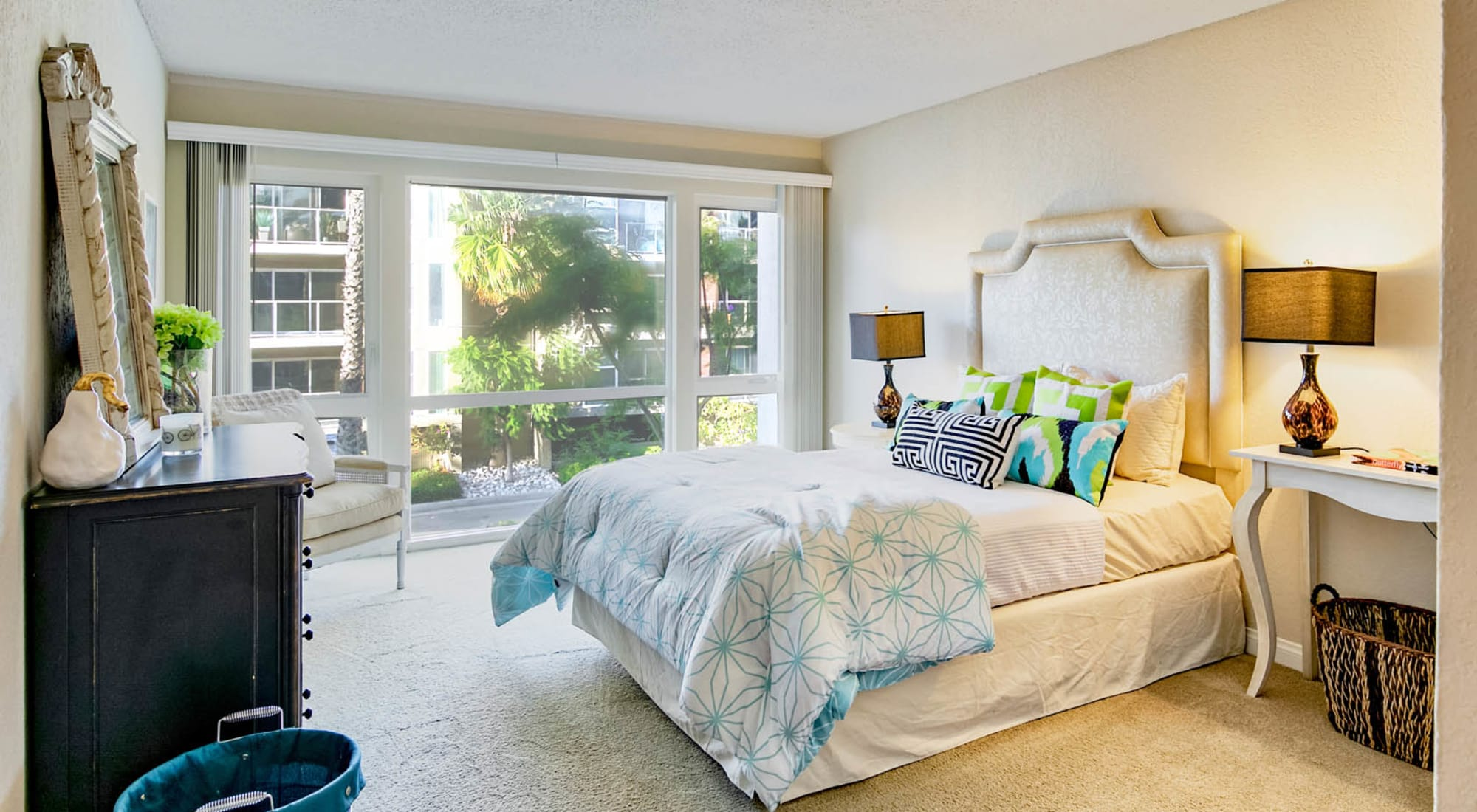 Model apartment's classically furnished primary bedroom with plush carpeting at The Tides at Marina Harbor in Marina Del Rey, California