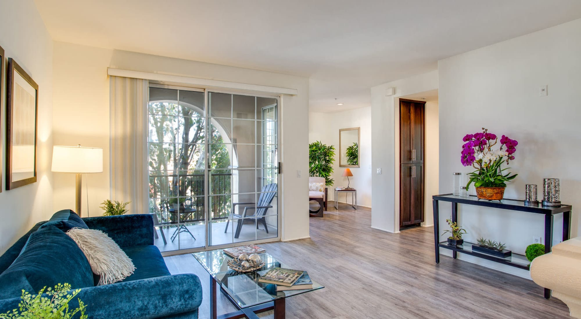 Model luxury home's well-furnished living area with sliding doors to the arched private balcony outside at L'Estancia in Studio City, California