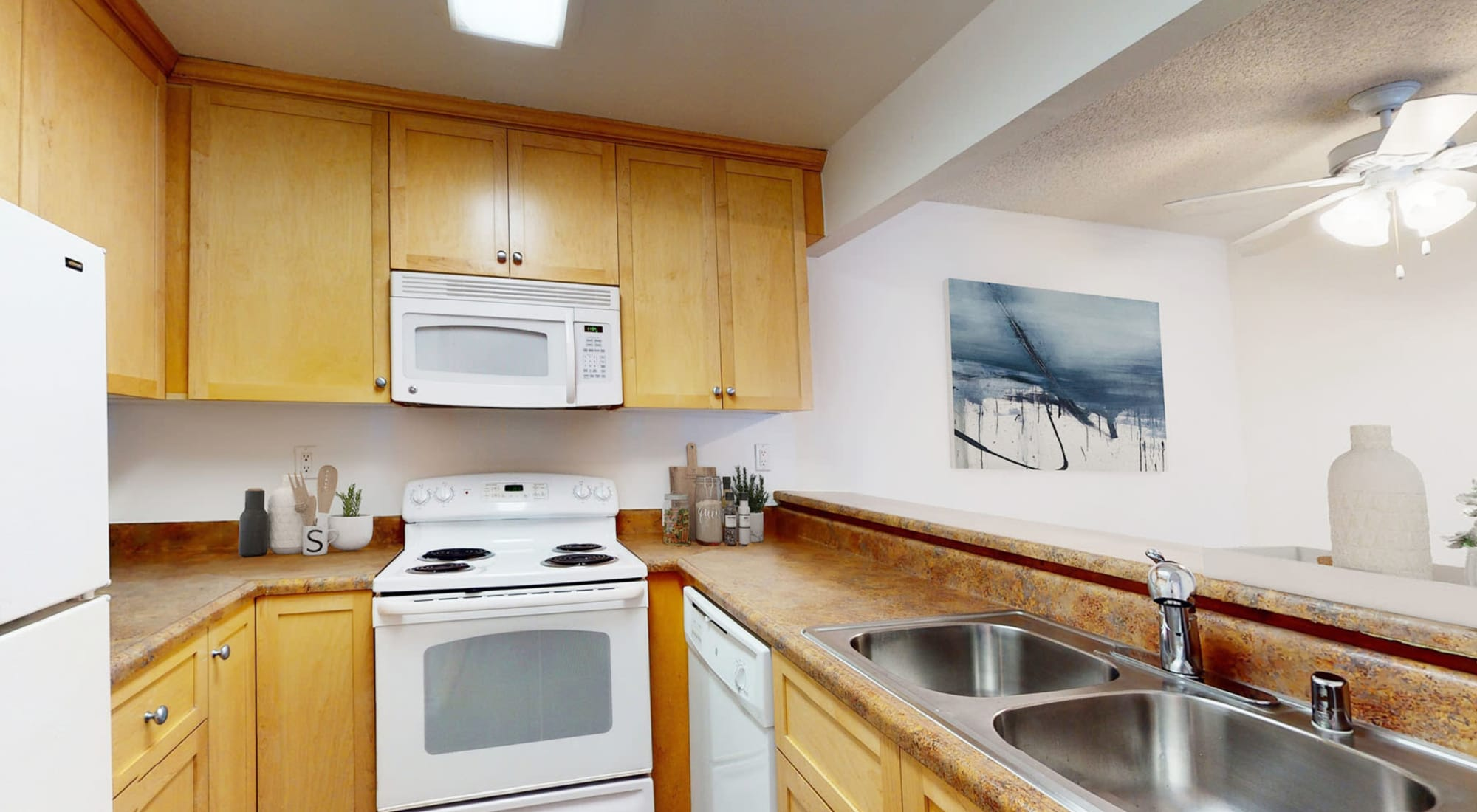 Modern kitchen with granite countertops and a dual-basin sink in a model apartment at Mariners Village in Marina del Rey, California