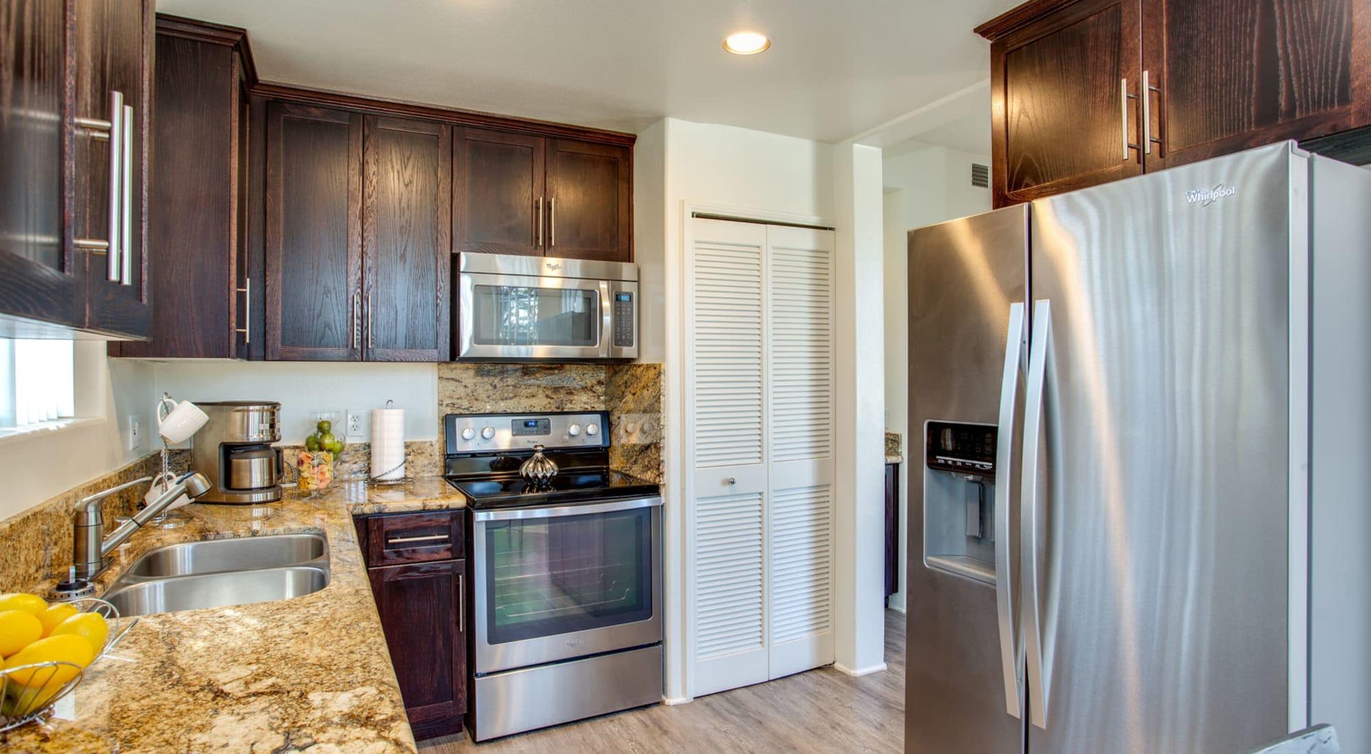 Granite countertops and espresso wood cabinetry in a model home's chef-inspired kitchen at L'Estancia in Studio City, California