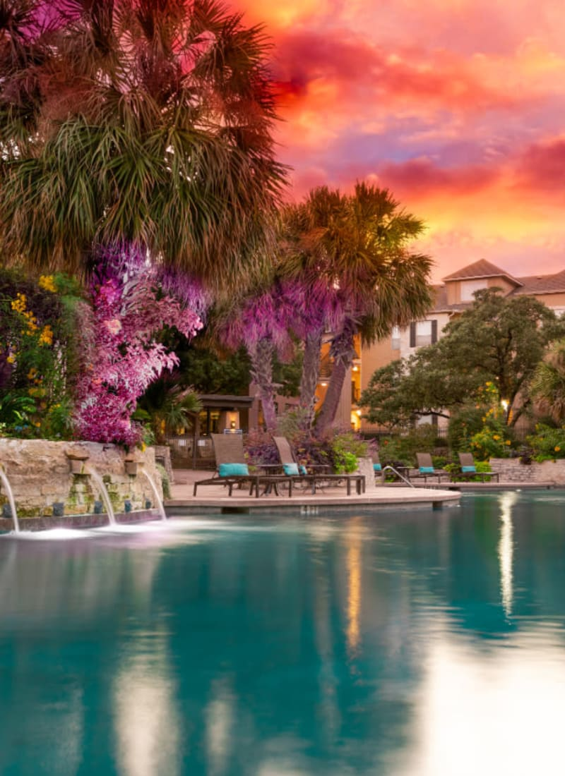 Resort style pool with water features as sunset at Marquis at Great Hills in Austin, Texas