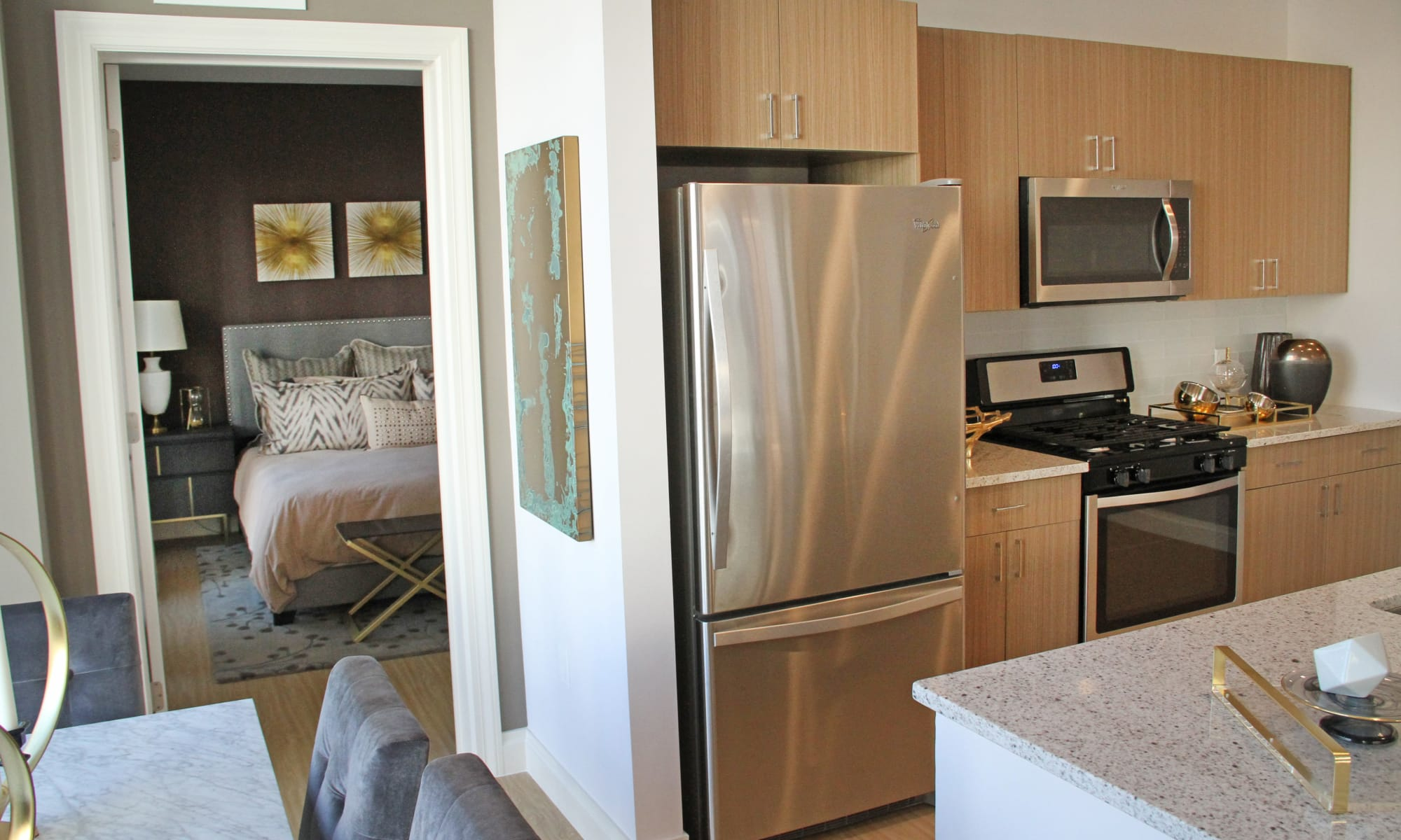 Kitchen and partial bedroom view at The Harper at Harmon Meadow
