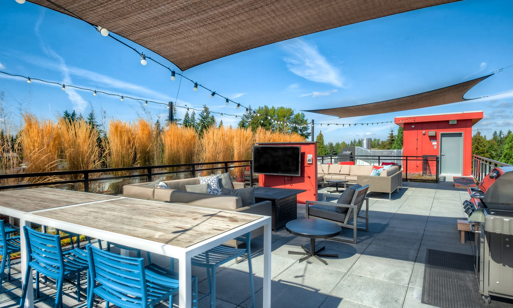 Rooftop deck and lounge area with TVs, couches, corn hole and BBQ at Tria Apartments in Newcastle, WA